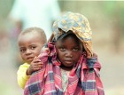 A girl and her younger brother orphaned in the Rwanda war at a refugee camp alongside Lake Kivu.