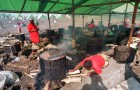 Dinner for many is prepared in an old oil drum at a refugee camp near Lake Kivu.