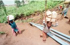 Children walk alongside the pipes which will, when connected, carry running water to the refugee camp near Lake Kivu.