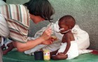A volunteer nurse cares for a sick baby girl at a refugee hospital in Rwanda.
