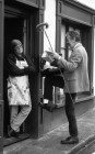 A determined woman fends off an equally determined doorstep salesman. 1/1/93. Ref G166/21.