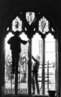 Ron Percy and his assistant replace a stained glass window in St. Mary's church, launceston.